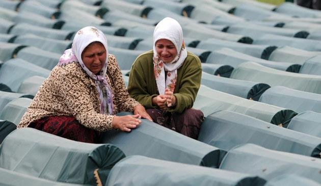 Bosnian women weep over the coffin of a relative before the memorial burial service for victims of the Srebrenica massacre at Potocari on Friday