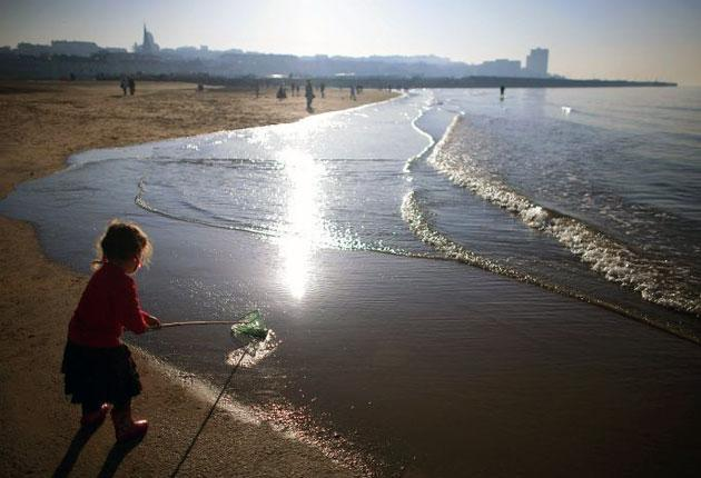 A girl goes fishing on a deserted Brighton beach. New figures show the number of foreign visitors to Britain has fallen for the first time in seven years
