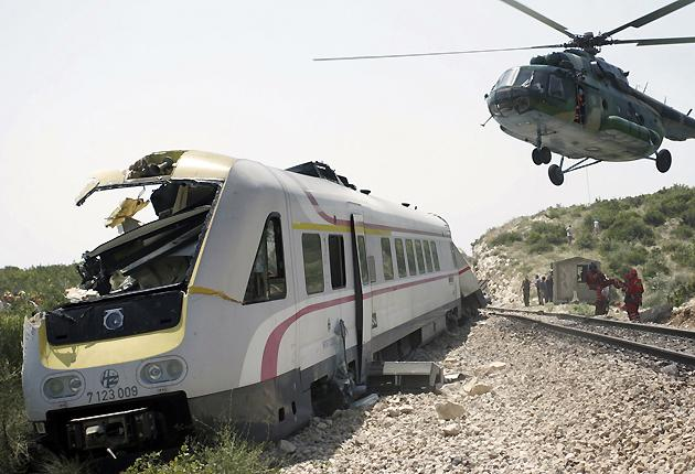An army rescue helicopter flies over a derailed passenger train near the Croatian Adriatic port of Split