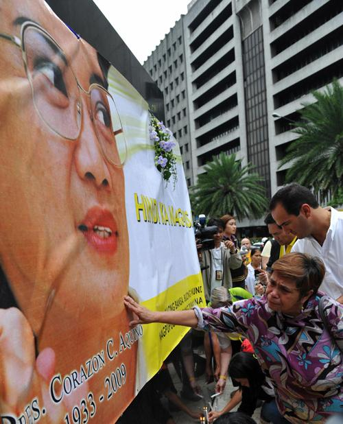A supporter touches a banner honouring late former Philippine president Corazon Aquino at the monument of her late husband Benigno Aquino in Manila