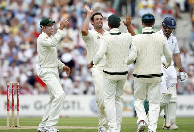 Australia's Ben Hilfenhaus (second left) celebrates taking the wicket of the England captain Andrew Strauss at The Oval yesterday