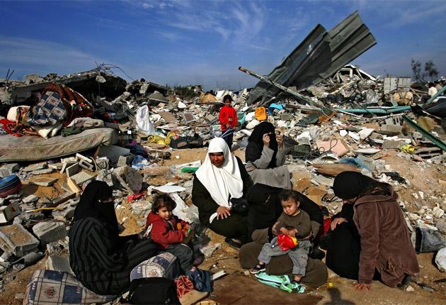 Palestinians sit among the rubble of homes destroyed by Israeli air strikes