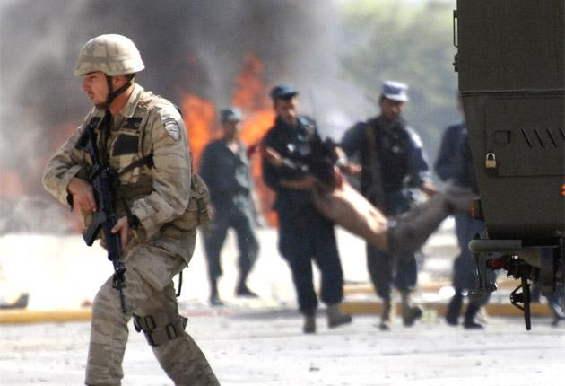 A Nato soldier takes position as Afghan police carry a man injured in a blast outside the military airport in Kabul yesterday