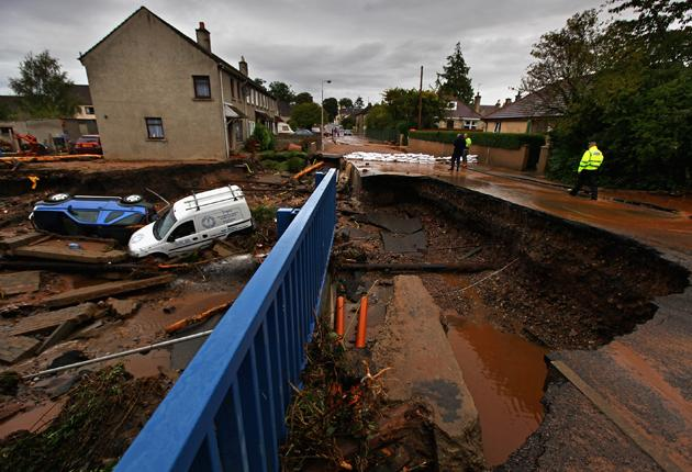 Police view the damage caused to a bridge in Burnbank, Fochabers, which was washed away as a result of flooding earlier this month