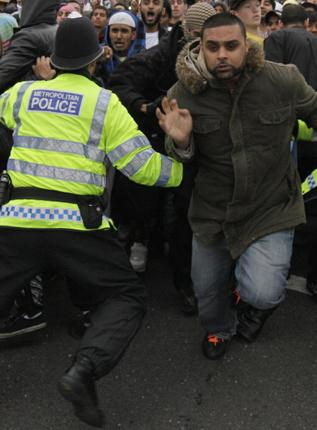 Police officers trying to control anti-fascist protesters charging against anti-Muslim protesters in the London suburb of Harrow last Friday
