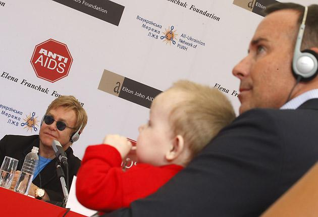 Elton John (left) listens to a question while his partner David Furnish holds a baby during a news conference in a hospital for HIV-positive children in the town of Makeyevka, outside Donetsk