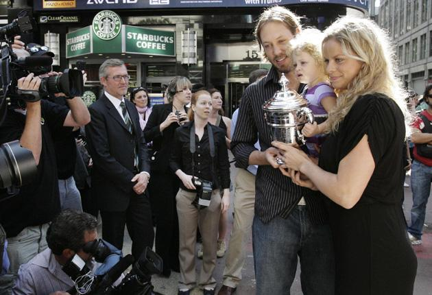 Kim Clijsters poses with the US Open trophy in Times Square alongside her husband and daughter Jada