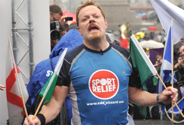 Drenched in sweat and rain Izzard crosses the finish line in London yesterday