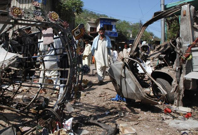 A man walks past destroyed vehicles at the site of a suicide bomb attack in Kohat, located in Pakistan's North West Frontier Province on September 18, 2009.