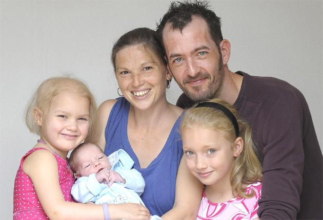 Nicola Tyler, 32, centre, with newborn Zac; Kelly, 6, left; father Dave Abbott, 38, right; and Chloe, 9