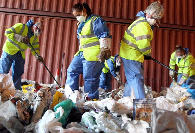 Environment Agency workers inspect a shipping container filled with refuse in Felixtowe, Suffolk