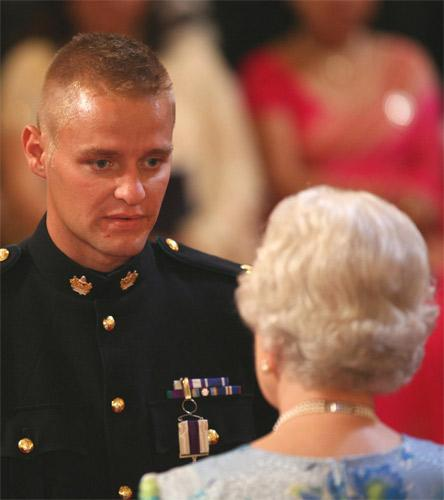 Corporal Michael Lockett is decorated with the Military Cross by the Queen at Buckingham Palace in June 2008