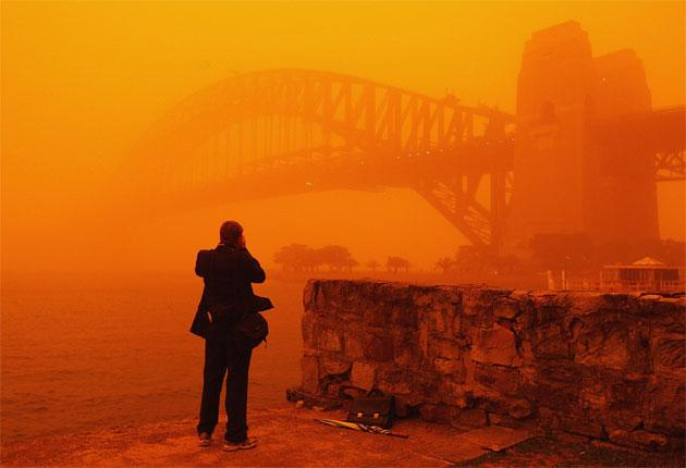 Sydney Harbour Bridge is obscured by the red dust cloud that enveloped the city