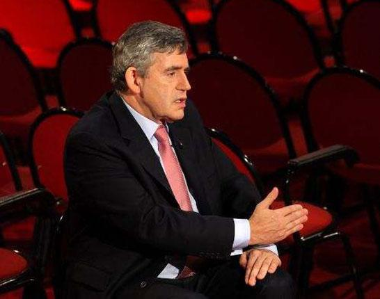 Gordon Brown cuts an isolated figure in the empty conference hall yesterday as he speaks to interviewers about The Sun's decision