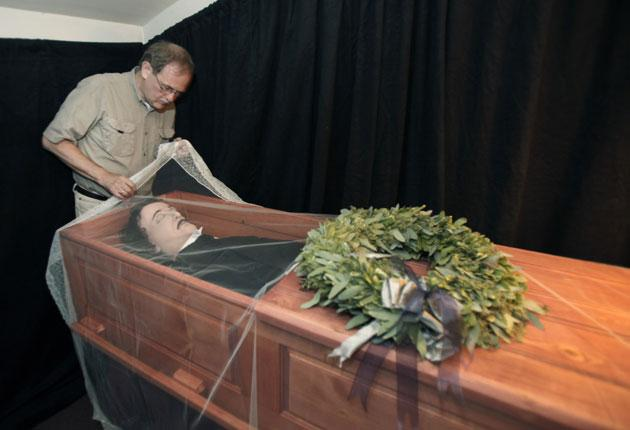 Jeff Jerome, curator of the Poe House and Museum, looks over a replica of the body of Poe