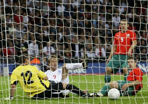 Peter Crouch scores past Belarus' goalkeeper Yury Zhevnov after evading the challenges of defenders Aleksandr Yurevich and Sergei Omelyanchuk