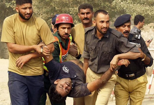 Pakistani policemen remove an injured colleague from a police training centre after gunmen attacked in Lahore