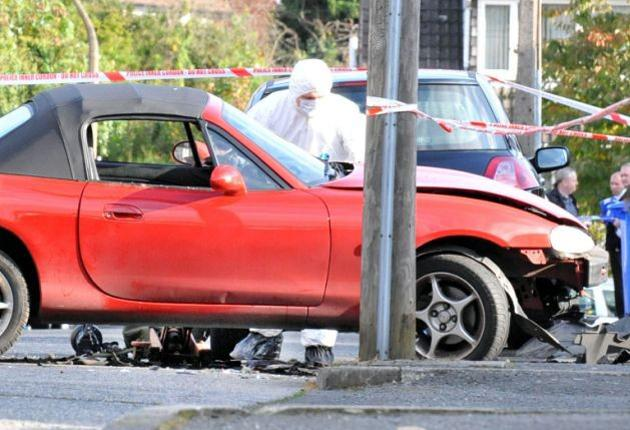 An Army bomb disposal expert examines the Mazda MX5 that was damaged by a booby trap planted by dissident republicans in east Belfast