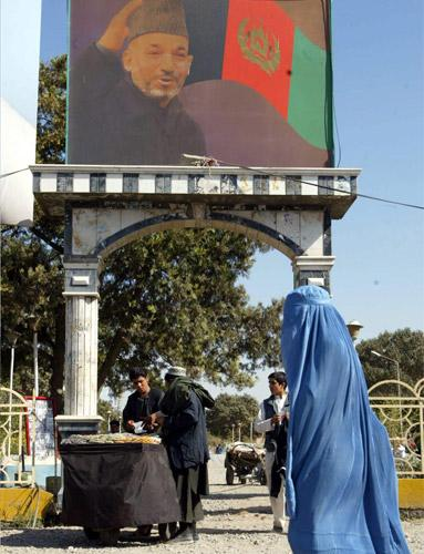 An Afghan woman passes an electoral billboard of President Karzai
