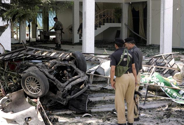 Pakistani police officers examine the wreckage from a bomb blast outside a health centre in Peshawar