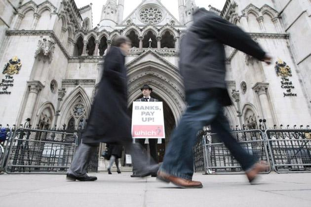 A man protests against bank charges outside The Royal Courts of Justice in central London