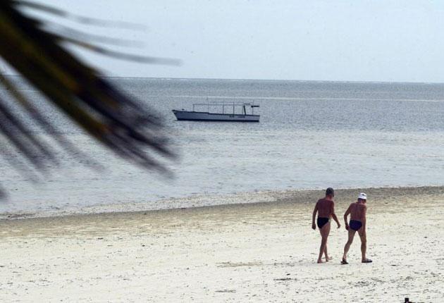Tourists walk at a beach in Mombasa