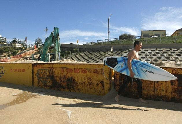 Asurfer walks past a construction site on Coogee Beach in Sydney