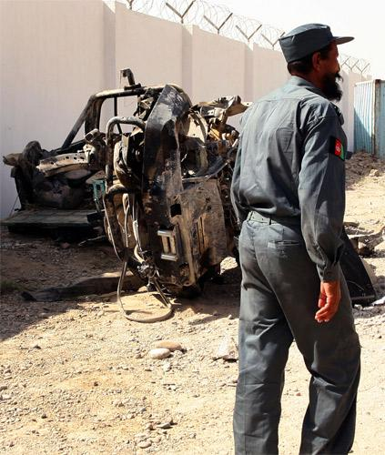 An Afghan police officer walks past the remains of a vehicle destroyed by a roadside bomb that has been placed outside the police compound in Nad-e-Ali