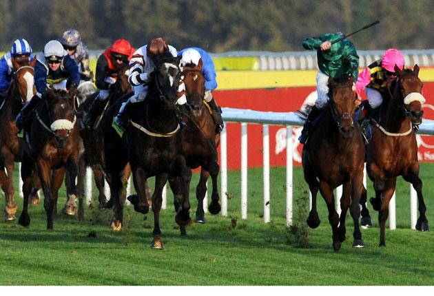 Charm School, ridden by Jimmy Fortune (second right), goes clear to win the November Handicap