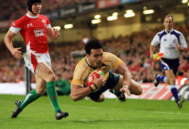 Australia's Digby Ioane dives in to score the opening try of the game during a thumping win over Wales at the Millennium Stadium last night