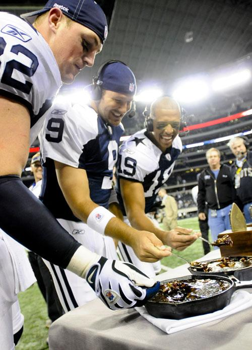 Dallas Cowboys players tuck into a Thanksgiving meal on the touchline
