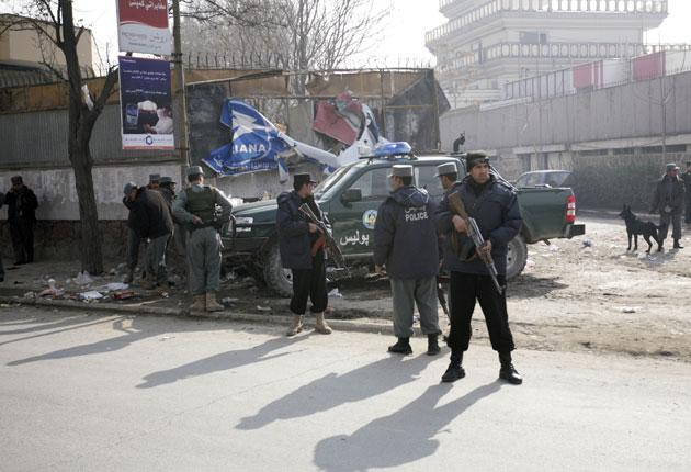 Afghan police officers stand guard near the site of a small explosion in Kabul yesterday