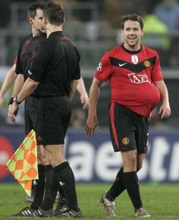 Michael Owen leaves the Wolfsburg pitch with the match ball up his shirt after scoring his hat-trick on Tuesday night