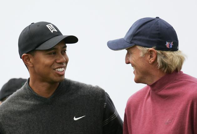 Tiger Woods (in happier times) shares a joke with Greg Norman