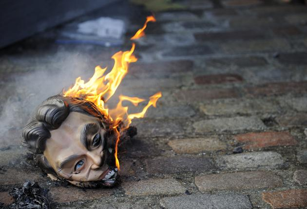 A burning Tony Blair mask was left outside the Chilcot inquiry by protesters angry at the former PM