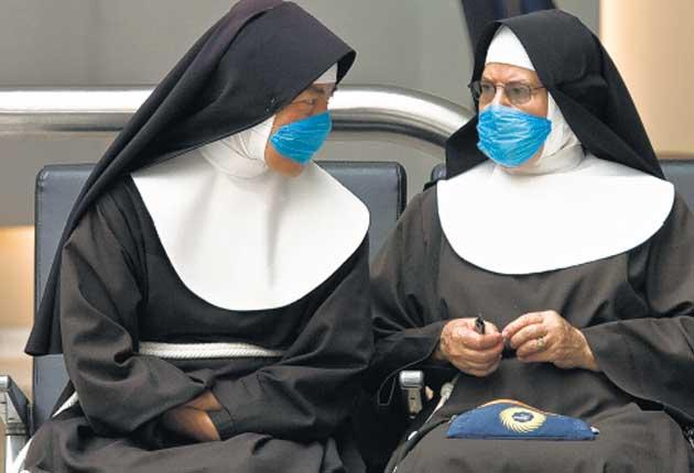 Fear factor: Two nuns at Mexico City's international airport wear masks to ward off swine flu as the threat of a pandemic looms large