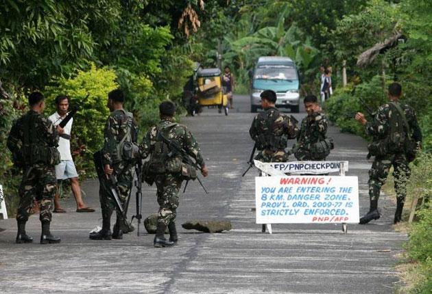 Filipino soldiers stop tourists entering the danger zone while villagers evacuate