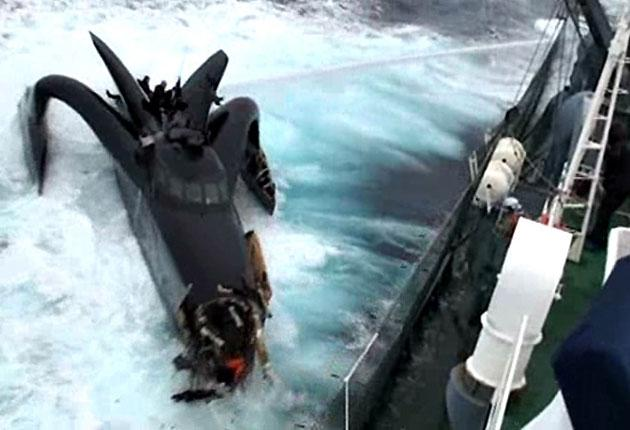 A frame grab from a video released by the Institute of Cetacean Research shows the crew of the Japanese ship Shonan Maru No. 2 spraying water at the Sea Shepherd Conservation Society's high-tech powerboat Ady Gil during a collision between the two vessels