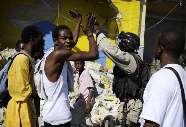 A Haitian policeman tries to stop the lootings in a street of Port-au-Prince.