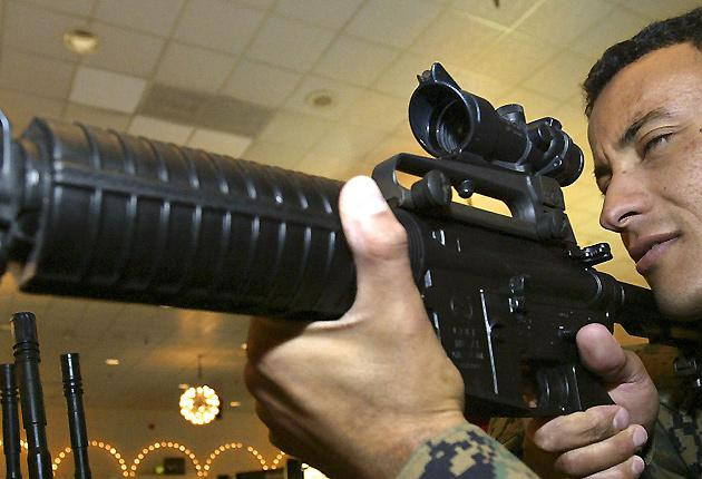 A US Marine tries out a Trijicon sight on an M-16 rifle during the Marine West 2004 Military Exposition in California