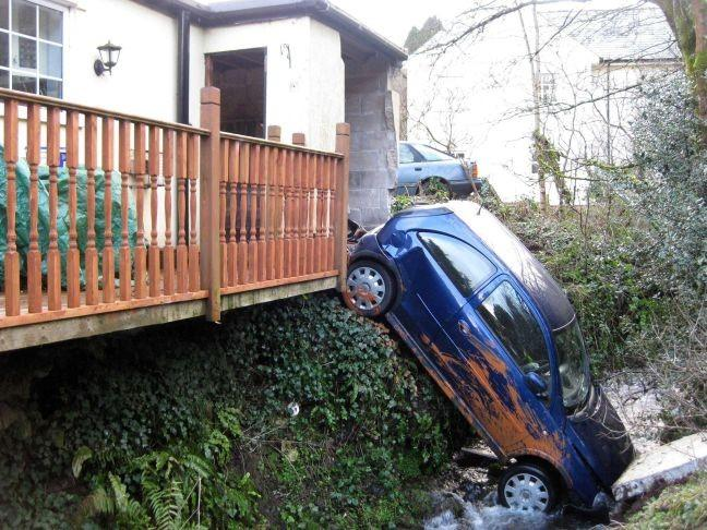 The scene after an elderly woman crashed through a garage and into a river in Chillaton, near Launceston, Cornwall