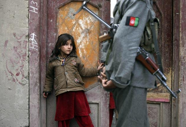 A girl watches an Afghan National Army soldier