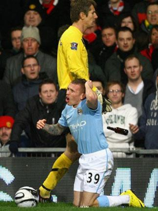 Craig Bellamy  reacts after being hit by objects thrown from the crowd during the Carling Cup Semi Final second leg against Manchester United