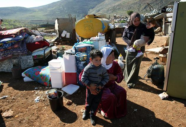 Palestinian women huddle amid their belongings after Israeli forces demolished their homes in the West Bank village of Khirbet Tana, near Nablus earlier this month