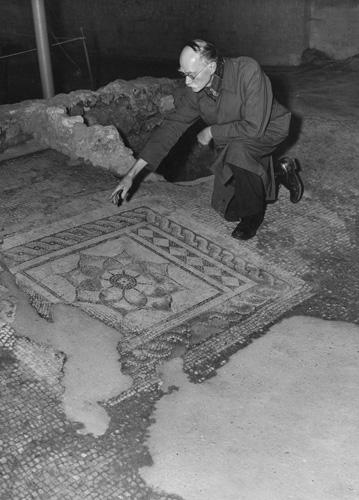 A curator points at a stretch of worn Roman mosaic pavement in a Canterbury museum in the 1950s.