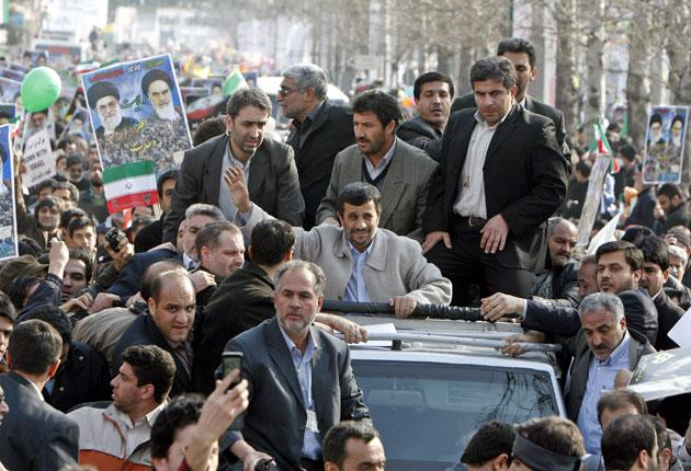 Iran's President Mahmoud Ahmadinejad greets thousands of supporters yesterday in Tehran before attending a rally marking the Islamic revolution of 1979. The celebrations dwarfed protests organised by supporters of the opposition green movement held elsewh