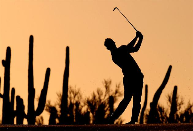 Luke Donald plays his approach shot on the first against a backdrop of the Arizona desert yesterday