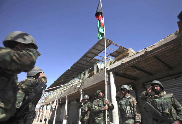 Afghan army officers salute their national flag in a ruined market in Marjah, Helmand province, yesterday