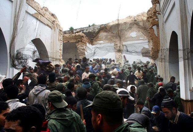 """People and rescue workers search for victims at the historic """"Bab Berdeayen"""" mosque which minaret has collapsed in Meknes"""