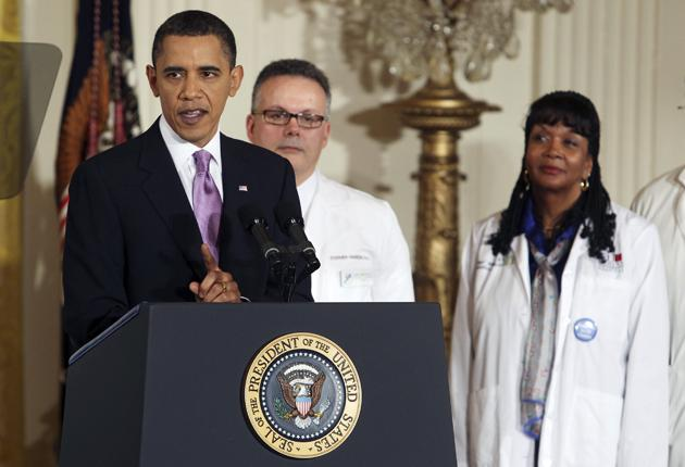 Barack Obama, surrounded by healthcare professionals, speaks about health reforms on Tuesday
